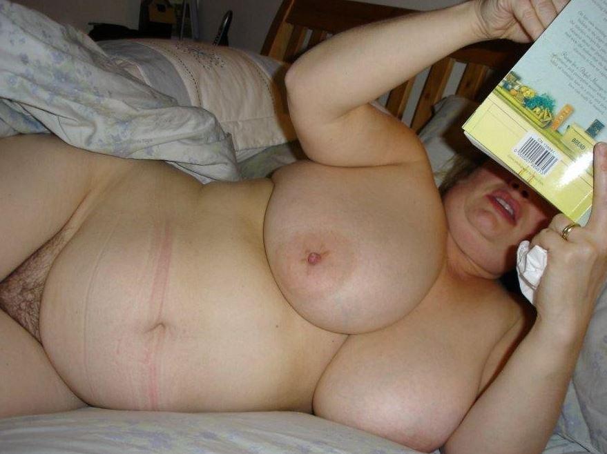 Mollige Frau mit dicken Titten liegt nackt auf dem Bett
